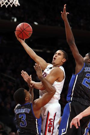 Arizona's Nick Johnson, center, shoots against Duke's Tyler Thornton (3) and Amile Jefferson, right, during the first half of an NCAA college basketball game in the NIT Season Tip-off tournament championship on Friday, Nov. 29, 2013, in New York. (AP Photo/Jason DeCrow)