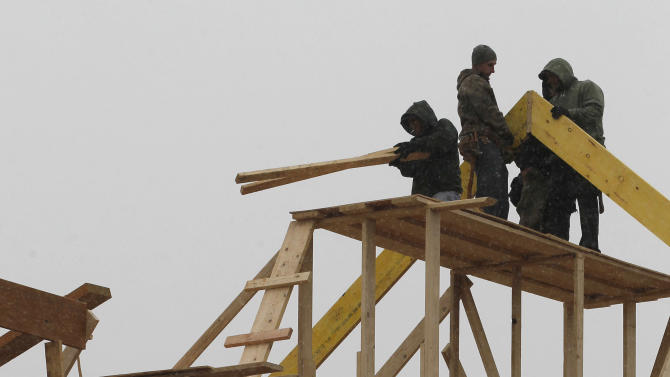 In this Feb. 8, 2012 photo, construction workers build a home in Newtown, Pa. A sharp drop in commercial building projects caused a slight decline in construction spending in January. But the dip comes after previous figures were revised much higher. (AP Photo/Alex Brandon)