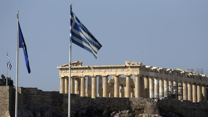 The Greek and European flags fly in front of the Parthenon of the Acropolis prior to a mass anti-government protest, in central Athens on Wednesday, Sept. 26, 2012. More than 50,000 people joined the union-led march during a general strike that ended in violence with clashes between riot police and hundreds of youths. The government in crisis-hit Greece is bracing for a new round of austerity measures despite being stuck in a four-year recession. (AP Photo/Dimitri Messinis)