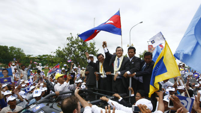 Sam Rainsy, center, president of Cambodia National Rescue Party (CNRP) greets his supporters together with his party's Vice President Kem Sokha, on Rainsy's left, on his arrival at Phnom Penh International Airport in Phnom Penh, Cambodia, Friday, July 19, 2013. Thousands of cheering supporters greeted Cambodian opposition leader Sam Rainsy as he returned from self-imposed exile Friday to spearhead his party's election campaign against well-entrenched Prime Minister Hun Sen. (AP Photo/Heng Sinith)