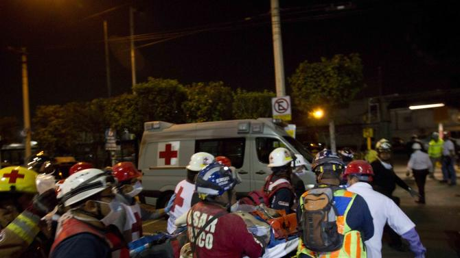 Rescue workers and firefighters an injured person after an explosion at an adjacent building to the executive tower of Mexico's state-owned oil company PEMEX, in Mexico City, Thursday Jan. 31, 2013. An explosion at the main headquarters of Mexico's state-owned oil company in the capital killed more than 10 people and injured some 80 as it heavily damaged three floors of the building, sending hundreds into the streets and a large plume of smoke over the skyline. (AP Photo/Eduardo Verdugo)