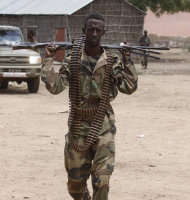 In this photo taken Thursday, Oct 11, 2012, Somali government soldier carries a weapon and ammunition after capturing Belidogle airport, Somalia from Al-shabab fighters. Somali government troops worked with African Union troops to secure the airport area. African union soldiers are preparing to move in convoy with supply vehicles from Balidogle airport to Mogadishu, a journey of about 100 Km (60 miles). The rough roads snake through rough terrain in this wide and dangerous land that the African Union peacekeepers have to move through every day to reach the newly seized bases in regions outside the capital. Despite the armored vehicles many troops are injured by the bush savvy militants. (AP Photo/Farah Abdi Warsameh)