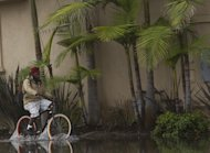 A cyclist drives the overflowed streets near the Pacific Coast Highway in the Sunset Beach area of Huntington Beach, Calif., Thursday, Dec. 13, 2012. Astronomical high tides have caused minor street flooding in some low-lying areas along the Southern California coast. (AP Photo/Damian Dovarganes)