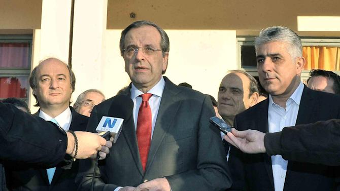 Greek Prime Minister Antonis Samaras (C) talks to journalists after voting at a polling station in Pylos on January 25, 2015
