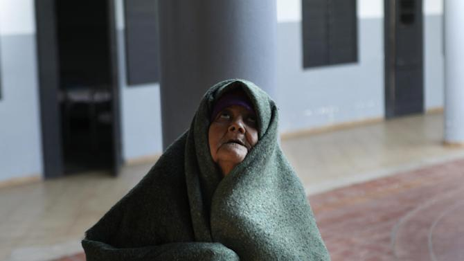 In this May 29, 2013 photo, a patient covers herself with a blanket in the courtyard of the Neuro-Psychiatric Hospital in Asuncion, Paraguay. Paraguay's only public psychiatric hospital is forced to feed hundreds of patients with donated food for lack of funding and there is no money for heating to protect patients from the biting chill during the winter months. (AP Photo/Jorge Saenz)