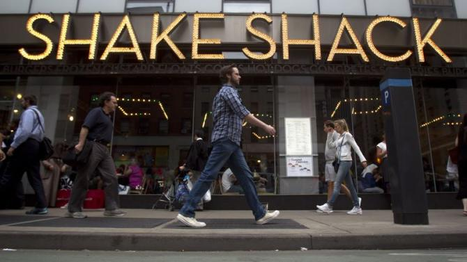 People walk past a Shake Shack restaurant in New York