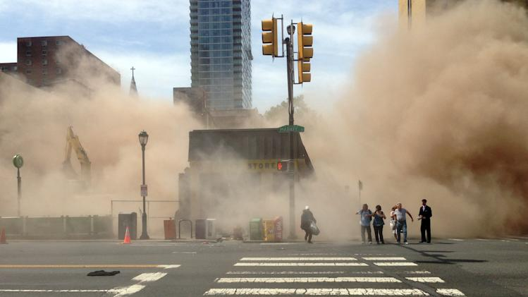 AP10ThingsToSee - A dust cloud rises as people run from the scene of a building collapse on the edge of downtown Philadelphia on Wednesday, June 5, 2013. At least six people were killed and 14 inured after the structure collapsed. (AP Photo/Jordan McLaughlin, File)