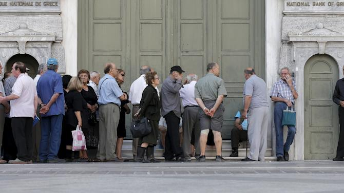 Pensioners wait in line in front of the main entrance of a National Bank branch to receive part of their pension in Athens