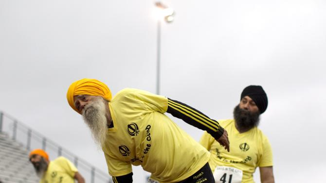Centenarian Fauja Singh, foreground, warms up with fellow runners before a series of races in Toronto Thursday Oct. 13, 2011.  One-hundred-year-old Singh, originally from India now living in London,  England, is competing in Toronto's Waterfront Marathon on Sunday.  (AP Photo/The Canadian Press, Chris Young)