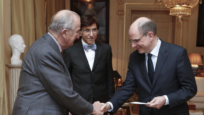 Belgium's newly appointed Minister of Finance Koen Geens, right, shakes hands with Belgium's King Albert II, after taking the oath of office at the Royal Palace in Brussels on Tuesday, March 5, 2013. Geens was appointed on Tuesday after Belgium's Minister of Finance Steven Vanackere resigned. At center is Belgium's Prime Minister Elio Di Rupo. (AP Photo/Bruno Fahy, Pool)