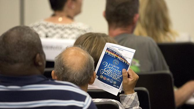 A man attending the U.S. Navy's Fleet Readiness Center Southwest's first LGBT pride event holds a program guide in San Diego