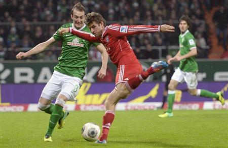 Werder Bremen's Luca Caldirola (L) and Bayern Munich's Thomas Mueller fight for the ball during their German Bundesliga first division soccer match in Bremen, December 7, 2013. REUTERS/Fabian
