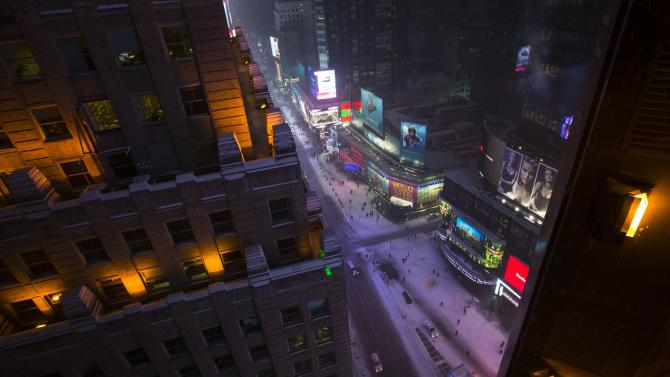 A view looking up 7th Avenue in Times Square in falling snow near dusk in New York