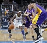 Denver Nuggets guard Ty Lawson, left, looks to work theball inside as Los Angeles Lakers guard Steve Blake, center, and center Andrew Bynum cover in the third quarter of the Nuggets&#39; 113-96 victory in Game 6 of the teams&#39;  first-round NBA basketball series in Denver on Thursday, May 10, 2012. (AP Photo/David Zalubowski)
