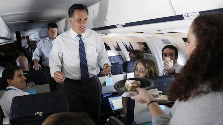 Ginger Gibson, national political reporter for Politico, right, offers two pieces of her birthday cake to Republican presidential candidate, former Massachusetts Gov. Mitt Romney as they fly to Long Island, NY, Thursday, Sept. 13, 2012. (AP Photo/Charles Dharapak)