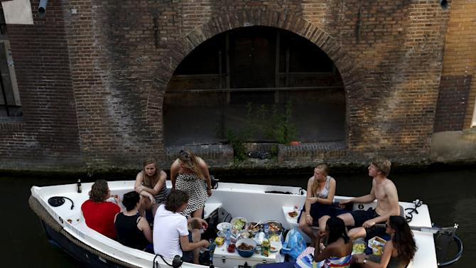 "People have a meal on a boat as they sails along the Oudegracht, or ""old canal"", in downtown Utrecht"
