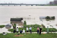Local residents look out towards a vegetable field submerged by floodwaters in Tosu, Saga Prefecture, on Saturday. About 400,000 people were ordered or advised to leave their homes in southwest Japan Saturday as heavy rain pounded the area for a third day