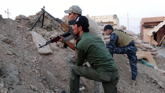 In this Thursday, Oct. 1, 2015 photo, Iraqi security forces, backed by Sunni and Shiite volunteers, clash with Islamic State group militants at the front line in the eastern suburbs of Ramadi, Anbar province, Iraq. (AP Photo)
