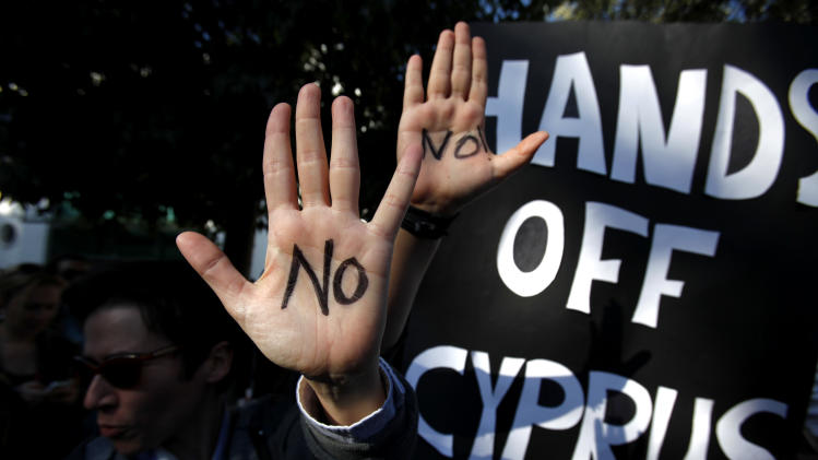 Protesters hold up their hands as they protest outside the parliament in capital Nicosia, Cyprus, Monday, March 18, 2013. A vote on a bailout package for Cyprus that includes an immediate tax on all savings accounts has been postponed until Tuesday evening. Yiannakis Omirou, the speaker of Parliament, said the delay was needed to give the government time to amend the deal reached over the weekend that prompted an outcry from those who thought their money was safe. In order to get euro 10 billion ($13 billion) in bailout loans from international creditors, Cyprus agreed to take a percentage of all deposits — including ordinary citizens' savings — an unprecedented step in Europe's 3 ½-year debt crisis. (AP Photo/Petros Karadjias)
