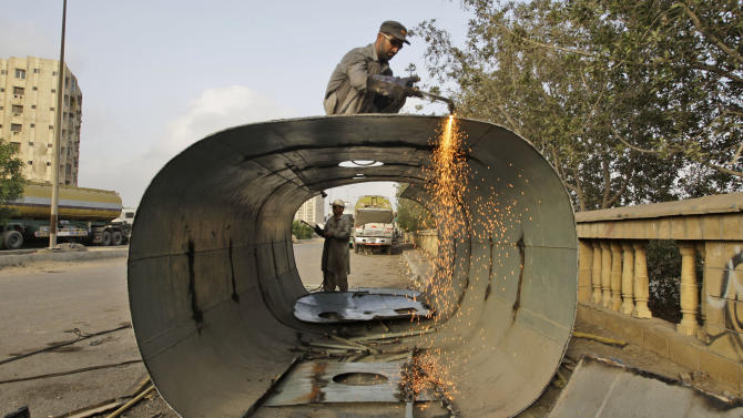 Pakistani mechanics yield the body of an oil tanker, which was used to transport NATO fuel supplies to Afghanistan, parked with other tankers in Karachi, Pakistan, Monday, July 2, 2012. (AP Photo/Shakil Adil)