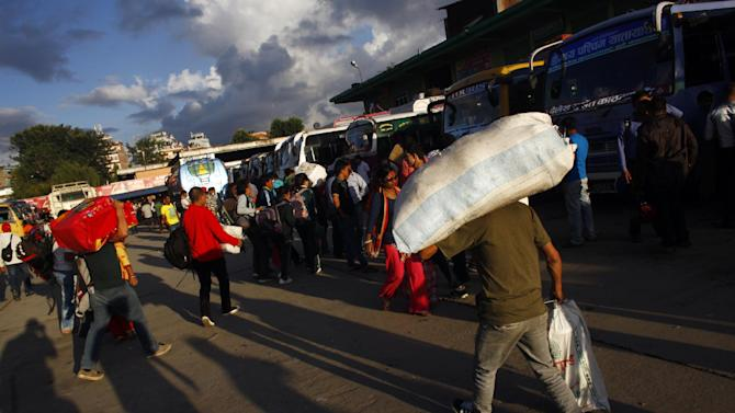 Nepalese people arrive to board buses as they head to their villages to celebrate Dashain festival, at the Gangabu bus park in Katmandu, Nepal, Monday, Sept. 22, 2014. The ten-day long Hindu festival that commemorates the victory of gods over demons begins on September 25. (AP Photo/Niranjan Shrestha)