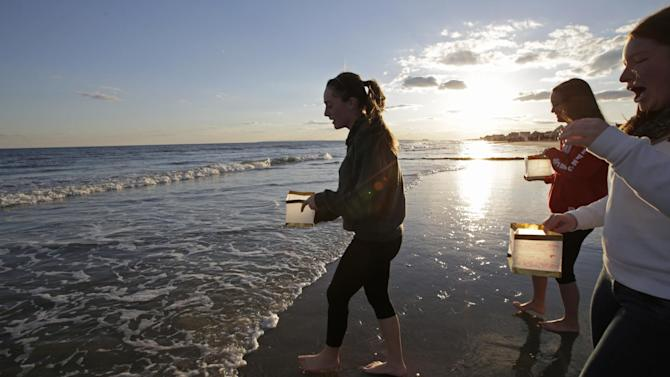 """Young women wade into the ocean to release lanterns with handwritten personal messages on them during a beachside ceremony """"Rockaways Rising: Hands Across the Sand,"""" commemorating the one year anniversary of Superstorm Sandy, Sunday, Oct. 27, 2013, in New York. The actual one year anniversary of Superstorm Sandy is Tuesday, Oct. 29. (AP Photo/Kathy Willens)"""