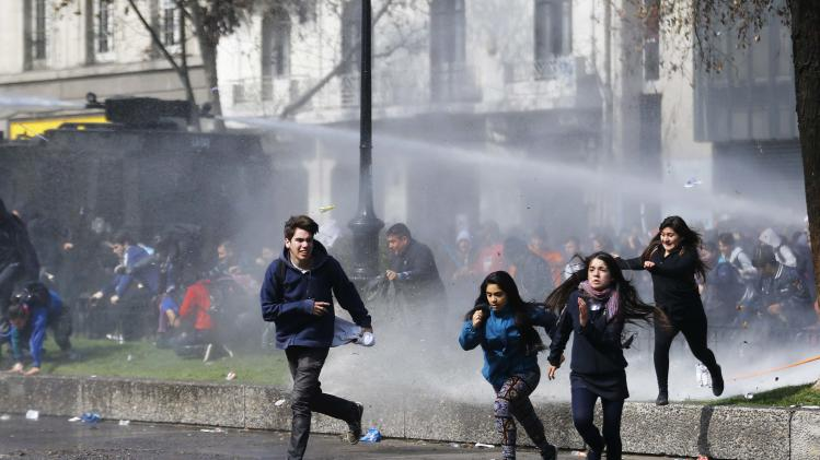 Students run away as riot police vehicle releases jet of water during demonstration against government to demand changes in education system in Santiago