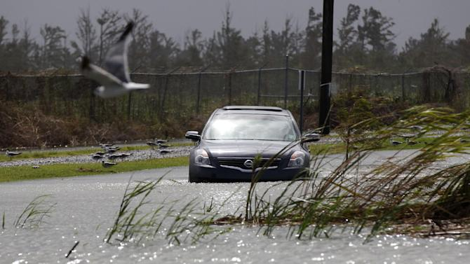 A car sits stranded in rising floodwaters from Isaac, which is expected to make landfall in the region as a hurricane this evening in Venice, La.,  the southernmost tip of the state, Tuesday, Aug. 28, 2012. Venice is outside the storm protection system and has been under mandatory evacuation. Forecasters at the National Hurricane Center warned that Isaac, especially if it strikes at high tide, could cause storm surges of up to 12 feet (3.6 meters) along the coasts of southeast Louisiana and Mississippi and up to 6 feet (1.8 meters) as far away as the Florida Panhandle. (AP Photo/Gerald Herbert)