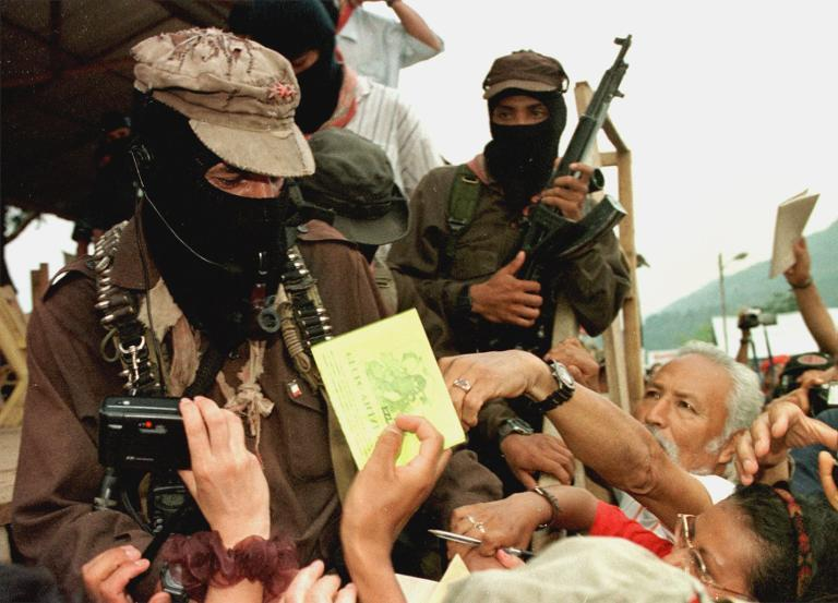 Subcomandante Marcos signs autographs during the opening of a meeting between Zapatista rebels and representatives of non-governmental organizations on May 8,1999, in La Realidad