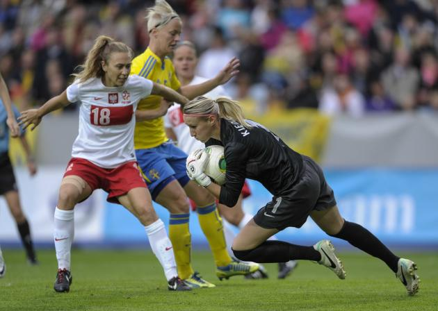Poland's goalie Katarzyna Kiedrzynek, right, grabs the ball in front of Sweden's Nilla Fischer, middle, with the help of Poland's Nicole Krzysik, left, during the ladies' football World Championships
