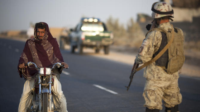 In this Sunday, Oct. 21, 2012 photo, an Afghan man on his motorcycle is stopped by a member of Afghanistan's elite Civil Order Police at a roadblock in Marjah, southern Helmand province, Afghanistan. As the U.S. and NATO close out their mission in Afghanistan preparing for the final withdrawal of combat troops by the end of 2014, the worry looms large that fresh outbursts of ethnically motivated fighting would send the country into a spiral of chaos and violence. (AP Photo/Anja Niedringhaus)