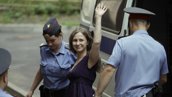 """Yekaterina Samutsevich, center, a member of feminist punk group Pussy Riot waves as she is escorted to a court room in Moscow, Russia, Monday, July 30, 2012. Three members of the band are facing trial for performing a """"punk prayer"""" against Vladimir Putin from a pulpit of Moscow's main cathedral before Russia's presidential election in March, in which he won a third term. (AP Photo/Mikhail Metzel)"""