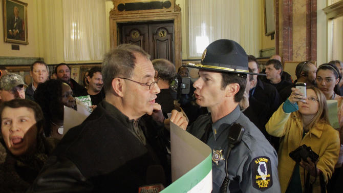 FILE - In this Feb 2, 2012 file photo, Henry Bayer, executive director of American Federation of State, County and Municipal Employees Council 31, left, as he is confronted by an Illinois Secretary of State police officer, right, while members of the AFSCME union protest in front of the governor's office at the state Capitol in Springfield. The ability of Illinois unions to withstand the pressures that broke down their colleagues in other states could be tested during a veto session beginning Tuesday, Nov. 5, 2013, as lawmakers try for the umpteenth time to confront the nearly $100 billion shortfall in the public-employee pension system, the largest in the nation. The Legislature is under pressure to consider slashing pension benefits or requiring employees to contribute more to their own retirement funds or to retire at a later age. (AP Photo/Seth Perlman, File)