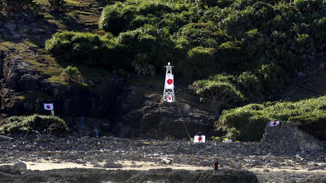 Japanese activists put up the national flags on Uotsuri island, one of the islands of Senkaku in Japanese and Diaoyu in Chinese, in East China Sea, Sunday, Aug. 19, 2012.   Japan's Coast Guard says a group of Japanese activists have landed on Uotsuri,  one of a group of islands at the center of an escalating territorial dispute with China. (AP Photo/Kyodo News) JAPAN OUT, MANDATORY CREDIT, NO LICENSING IN CHINA, HONG KONG, JAPAN, SOUTH KOREA AND FRANCE