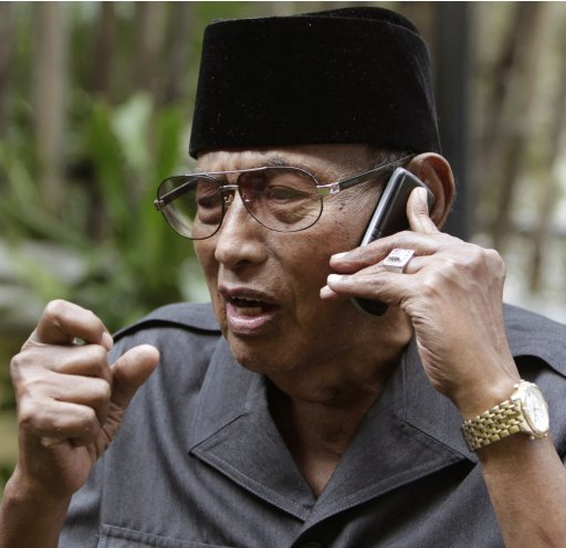 Sultan of Sulu Jamalul Kiram III talks on a mobile phone to his brother Prince Agbimudin during a news conference in Alabang, Metro Manila