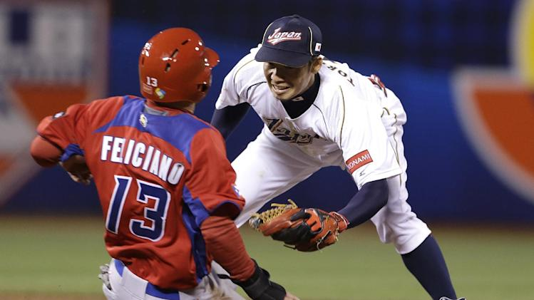 Japan's Takashi Toritani, right, waits to tag out Puerto Rico's Jesus Feliciano trying to steal second base during the fifth inning of a semifinal game of the World Baseball Classic in San Francisco, Sunday, March 17, 2013. (AP Photo/Eric Risberg)
