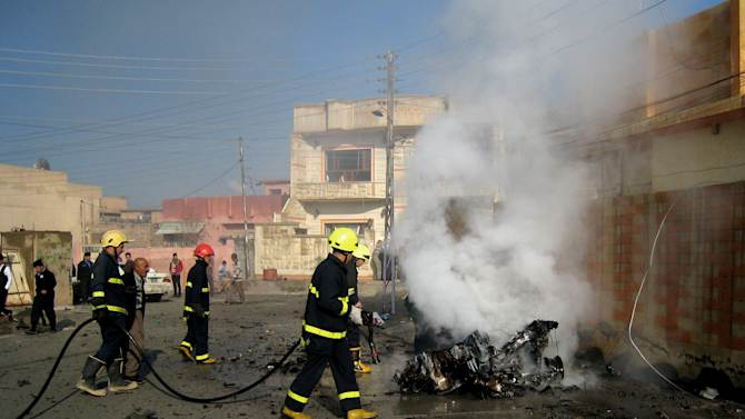 Iraqi firefighters distinguish a fire at the scene of a bomb attack in Kirkuk, 180 miles (290 kilometers) north of Baghdad, Iraq, Tuesday, Nov. 27, 2012. Three parked car bombs exploded Tuesday morning simultaneously in the city of Kirkuk, home to a combustible mix of Kurds, Sunni Arabs and Turkomen who all claim rights to the city, killing and wounding scores of people, police said. (AP Photo/Emad Matti)