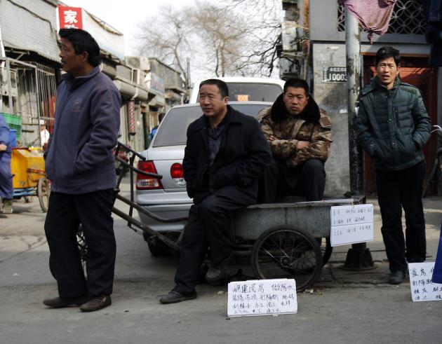 "Jobseekers with signs mentioning their skills wait for employers at a market street in a Hutong, Chinese for ""small alley"", in Beijing"