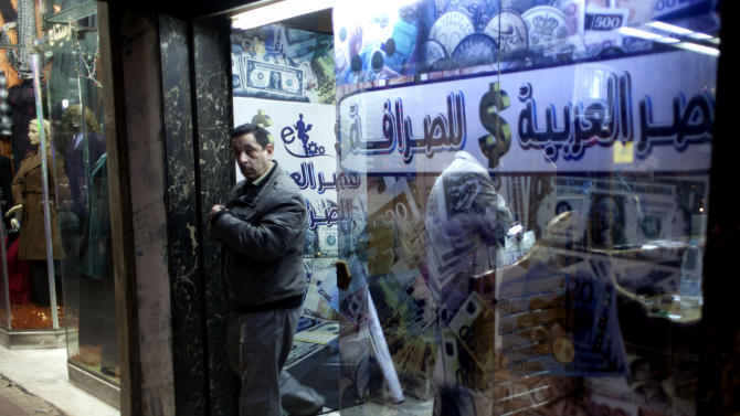 """An Egyptian man leaves after changing foreign currency at a currency exchange office, Arabic reads, """"Arabian Egypt for Exchange,"""" in Cairo, Egypt, Sunday, Jan. 6, 2013. Egypt swore in 10 new ministers on Sunday in a Cabinet shake-up aimed at improving the government's handling of the country's ailing economy ahead of talks this week with the International Monetary Fund over a badly needed $4.8 billion loan. (AP Photo/Nasser Nasser)"""