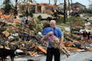 FILE - In this May 22, 2011, file photo a man carries a young girl who was rescued after being trapped with her mother in their home after a tornado hit Joplin, Mo. The tornado, that killed 158, is one of the 10 deadliest tornadoes in the United States since 1900. (AP Photo/Mike Gullett, File)
