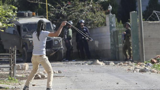 Palestinian protester uses a slingshot to throw stones at Israeli troops during clashes following a protest against the nearby Jewish settlement of Qadomem, in the West Bank village of Kofr Qadom