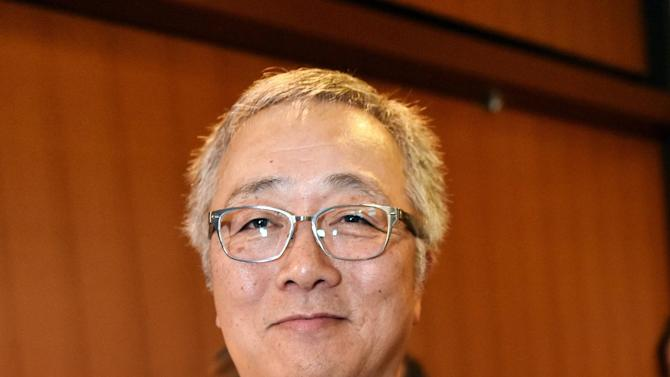 A photo taken on December 12, 2014 shows Japanese comic artist Katsuhiro Otomo smiling at the French embassy in Tokyo