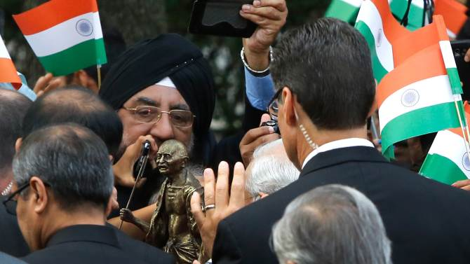 A supporter give a statuette of Gandhi to Modi as he arrives to pay homage at the full-sized Ghandi statue in front of the Indian Embassy in Washington