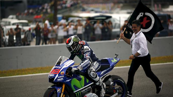 Yamaha MotoGP rider Jorge Lorenzo of Spain stops his bike on the track to take a flag after winning the Spanish Grand Prix in Jerez de la Frontera