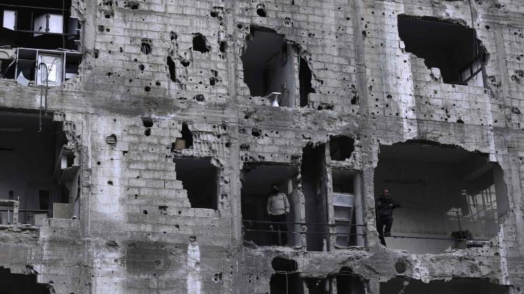 Men stand in a damaged building in the Duma neighbourhood of Damascus
