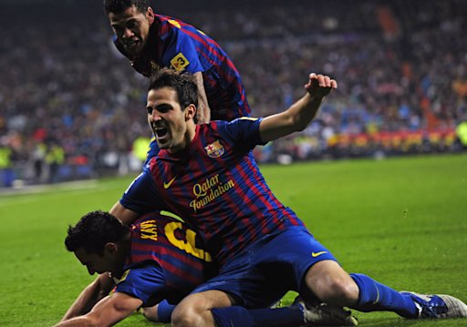 Barcelona's midfielder Xavi Hernandez (down), Barcelona's midfielder Cesc Fabregas (C) and Barcelona's Brazilian defender Dani Alves celebrate after Real Madrid's Brazilian defender Marcelo scored an own goal during the quot;El clasicoquot; Spanish League football match Real Madrid against Barcelona at the Santiago Bernabeu stadium in Madrid on December 10, 2011. AFP PHOTO/JAVIER SORIANO (Photo credit should read JAVIER SORIANO/AFP/Getty Images)