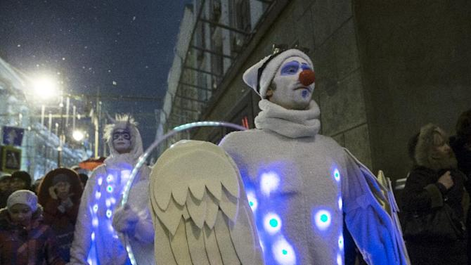 People dressed in illuminated angel costumes parade to mark Christmas Day in central Moscow, Russia, on Thursday, Dec. 25, 2014.  (AP Photo/Pavel Golovkin)