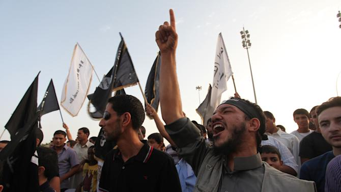 """Libyan followers of the Ansar al-Shariah Brigades chant anti-U.S. slogans during a protest in front of the Tibesti Hotel, in Benghazi, Libya, Friday, Sept. 14, 2012, as part of widespread anger across the Muslim world about a film ridiculing Islam's Prophet Muhammad.  One of the leading suspects in an attack that killed the U.S. ambassador and three other Americans is the Libyan-based Islamic militant group Ansar al-Shariah, led by former Guantanamo detainee Sufyan bin Qumu. The group denied responsibility in a video Friday but did acknowledge its fighters were in the area during what it called a """"popular protest"""" at the consulate, according to Ben Venzke of the IntelCenter, a private analysis firm that monitors Jihadist media for the U.S. intelligence community. (AP Photo/Mohammad Hannon)"""