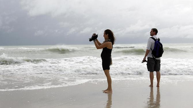 Tourists Stephanie and Dan Koch of Atlantic City, N.J. take a photograph of high surf as Hurricane Sandy passes offshore to the east, Friday, Oct. 26, 2012, in Miami Beach, Fla. Hurricane Sandy left at least 21 people dead as it moved through the Caribbean, following a path that could see it blend with a winter storm and reach the U.S. East Coast as a super-storm next week. (AP Photo/Lynne Sladky)