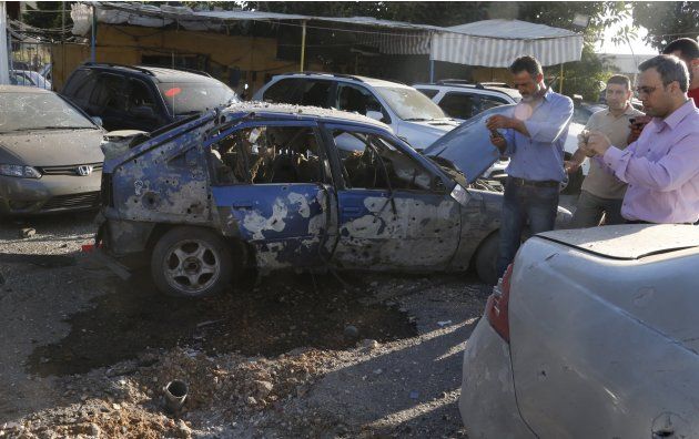 Residents inspect the remain of one of two rockets that hit residential area in Beirut suburbs